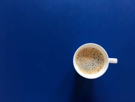Hot Americano coffee in white cup on dark blue table background. Bubble and foam cover on surface with copy space top view