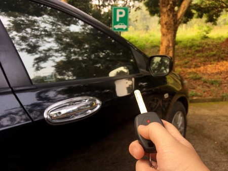 Woman hand press remote control of car key at parking to lock or unlock the car door.