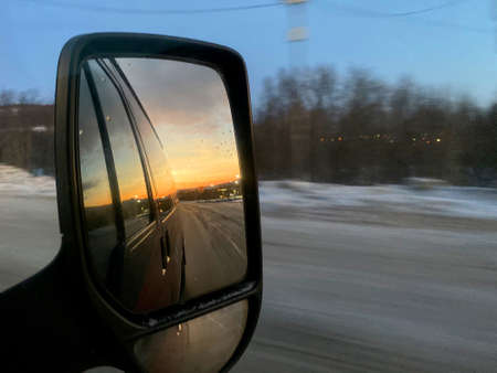 Sunrise in the morning reflect inside car side mirror during road trip in winter season.