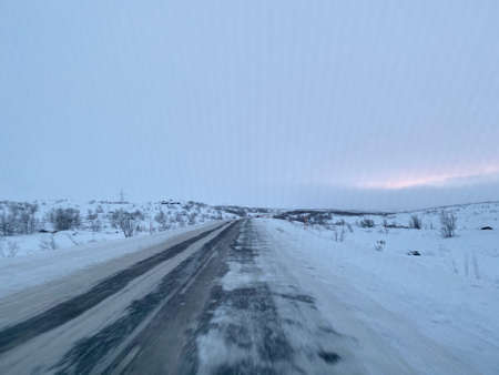 Empty road covering by white snow and some dry grass at side way with cloudy climate in winter season.
