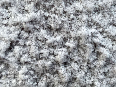 Closed up snowflakes on the ground in winter season. Beautiful contrast between white ice and brown land background.