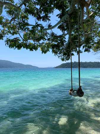 Transparent sea wave under green branch with wooden swing. Beautiful blue sea and white sand on the beach under blue sky.
