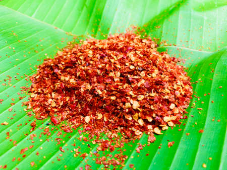Mashed dried red hot chili on fresh green banana leaf, Food ingredient for spicy recipe.