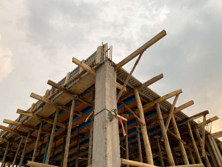 Home construction with wooden scaffolding for building from bottom view under cloudy sky Imagens