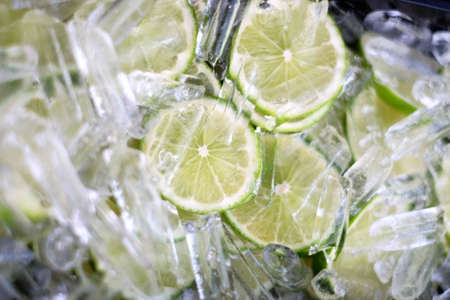 Selective focus of Juicy lime slice circle shape stacking inside small ice. Freshness and cool ingredient