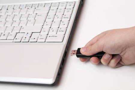 plugging: plugging the laptop with a usb on white background Stock Photo
