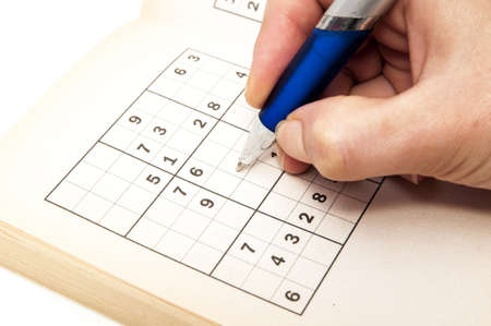hand making a sudoku on a white background