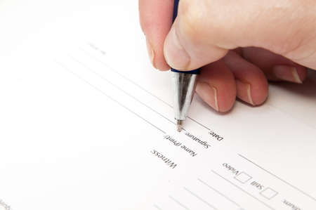 hand signing an agreement on a white background photo