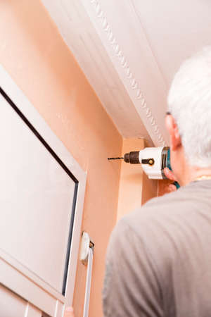 making hole: worker making a hole in the wall to mount curtains Stock Photo
