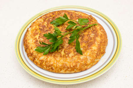 Spanish omelette with parsley on a white background photo