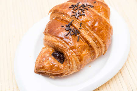 Chocolate croissant on a wooden background photo