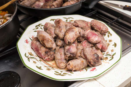 veal rolls with bacon, cheese and plum on a kitchen plate Imagens
