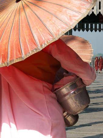 nun with pink dress and umbrella, walking on a bath bridge at Mandalay, Myanmar