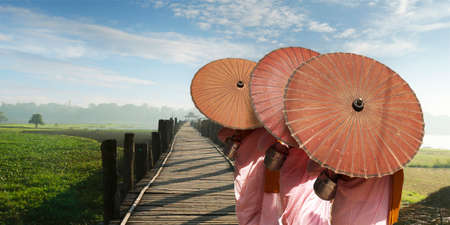 Nun with pink dress and umbrella, walking on the bath bridge at Mandalay, Myanmar