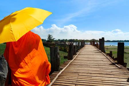 monk with umbrella, walking on a bath bridge at Mandalay, Myanmar
