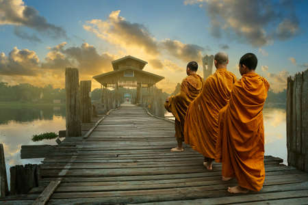 Monks walking on a bath bridge at Mandalay, Myanmar
