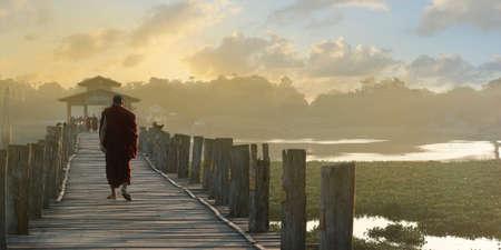 Monk walking on a bath bridge at Mandalay, Myanmar