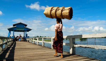 worker carrying basket on a bath bridge at Mandalay, Myanmar