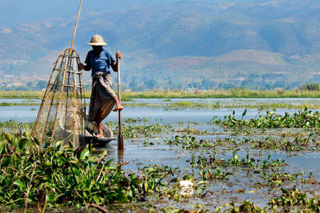 fisherman fishing with net in lake -myanmar