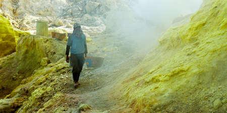 MINER COLLECTING SULFUR ON KAWAH IJEN VOLCANO IN JAVA ISLAND-INDONESIA