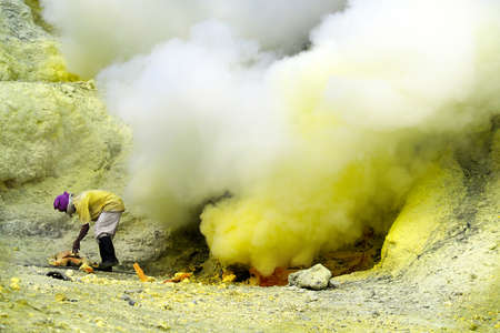 MINER COLLECTING SULFUR ON KAWAH IJEN VOLCANO IN JAVA ISLAND-INDONESIA Stock Photo