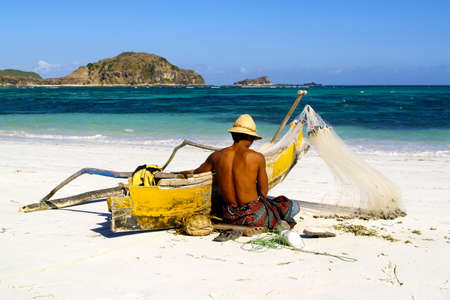 FISHERMAN REPAIRING NET HIS ON THE WHITE SAND BEACH
