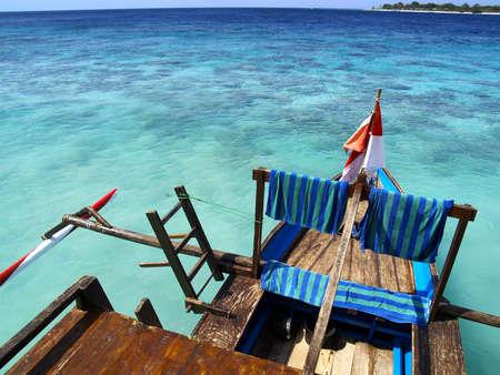 balijska łódź na białej, piaszczystej plaży