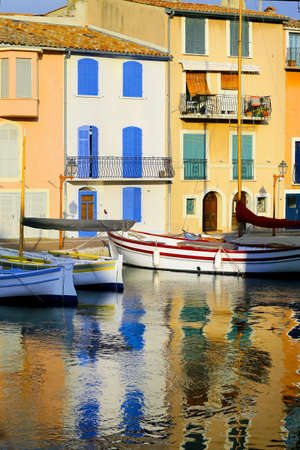 facade of mediterranean building with colorful shutter with river and boat