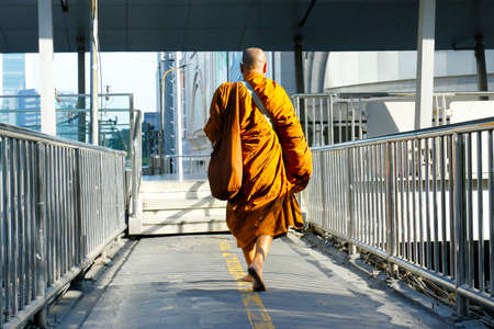 monk with orange robe walking in the street in bangkok -Thailand