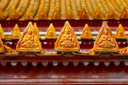 orange roof tiles on buddhist temple with design of buddha
