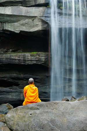 Monks doing meditation in front of a waterfall in thailand