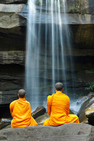 Monks doing meditation in front of a waterfall in thailand Stock fotó