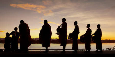 silhouette of monks dressing orange robe during reception of alms, on the shore of the mekong river