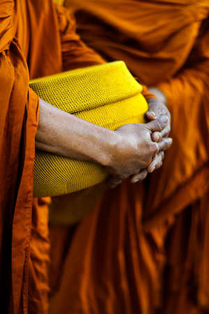 hand of monk dressing orange robe, holding bowl during reception of alms, around buddhist temple