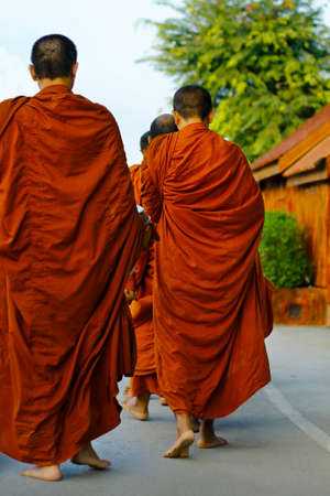 monks dressing orange robe during reception of alms, around buddhist temple