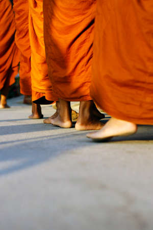 feet of monks dressing orange robe during reception of alms, around buddhist temple