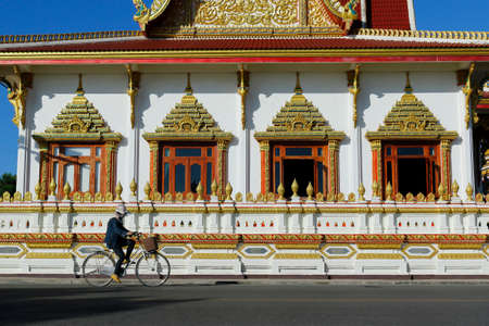 woman ridding bicycle in front of a buddhist temple in thailand