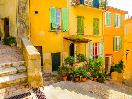 Narrow street in the Mediterranean city. Bright yellow houses in the Villefranche-sur-Mer, of the Cote d'Azur, France Imagens