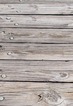 Old, cracked, faded timber planks with tree nails and knothole in close up Stock Photo