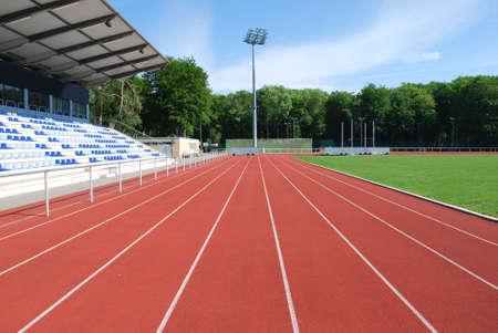 Tartan raceway in a modern stadium with empty grandstand on the left