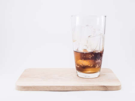 two and two thirds: one of thirds soft drink is cool with  two of thirds ice cubes in glass on wood squares