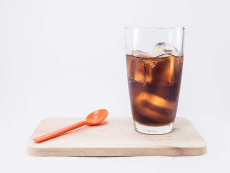 two and two thirds: two of thirds soft drink is cool and ice cubes in glass near orange spoon on wood squares