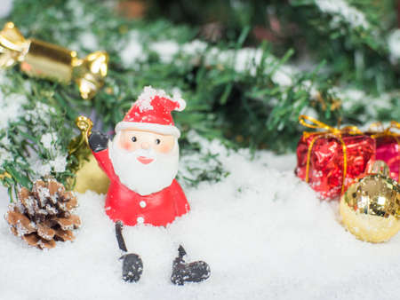 Santa claus doll and glod christmas balls and red box in the snow. Copy and paste for background, Concept decoration of christmas