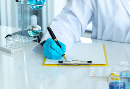 Chemist writes down experiment results in laboratory