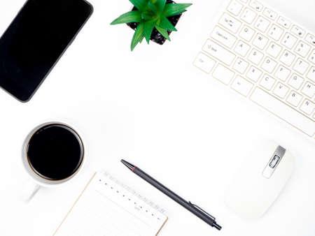 Mesa de escritorio de oficina blanca moderna con teclado, café, teléfono inteligente y otros suministros de oficina necesarios, vista superior con espacio de copia Foto de archivo
