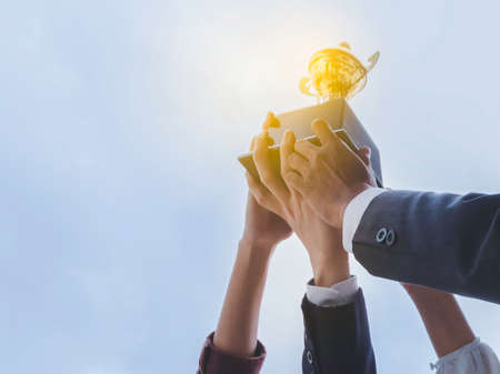 The best team helped each other reach their goals target to success. The hand of a business man and business women pick up the trophy and celebrate together. Teamwork of successful concept Stock Photo