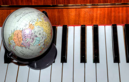 globe on piano can symbolize worldwide concert tour or sales photo