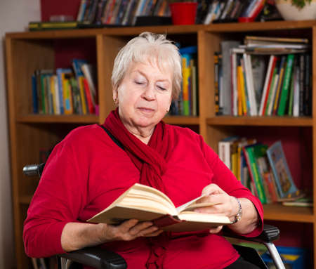 women subtle: female senior in wheelchair is reading a book Stock Photo