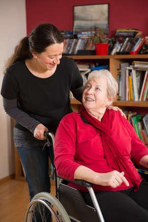 agradecimiento: mayor femenino en silla de ruedas en su casa