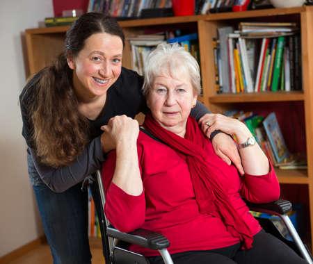 agradecimiento: mayor femenino en silla de ruedas con dependientes